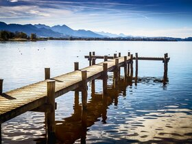 Bootssteg am Chiemsee mit Bergpanorama